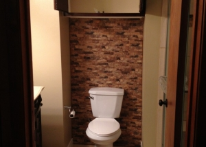 Cabinet, toilet and stone backsplash
