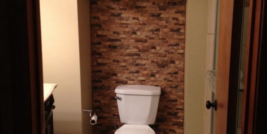 Cabinet, toilet and stone backsplash